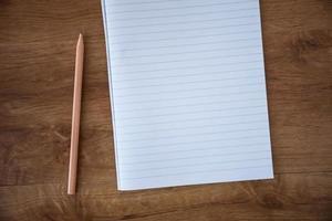 caderno em branco com lápis na mesa de madeira, conceito do negócio foto