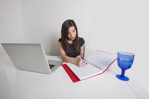 jovem empresária escrevendo no diário na mesa de escritório foto