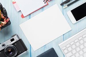 mesa de escritório com suprimentos, câmera e cartão em branco