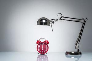 iluminando o despertador vermelho com lâmpada de mesa foto