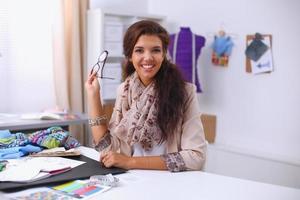 designer de moda feminina sorridente, sentado na mesa do escritório foto