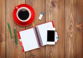 mesa de escritório com suprimentos e xícara de café