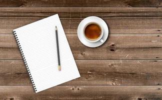 bloco de notas com uma xícara de café na mesa de madeira. foto