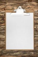prancheta com uma folha de papel em branco na mesa de madeira foto