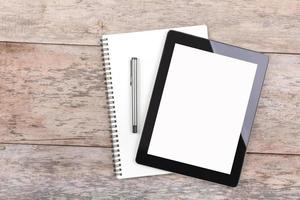 tablet e bloco de notas em uma área de trabalho de madeira foto