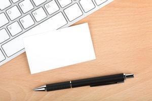 cartões de visita em branco sobre o teclado na mesa de escritório