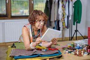 costureira olha para um tablet digital em sua oficina foto