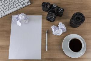 área de trabalho com folha em branco da câmera e café foto