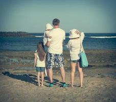 jovem família na praia foto
