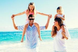 família feliz na praia foto