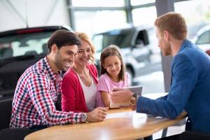 jovem família na concessionária de carros foto
