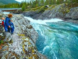 família perto de cachoeiras de rio de montanha (norge) foto