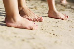 família descalça na areia foto
