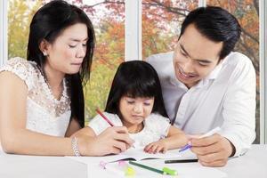 família moderna fazendo lição de casa na mesa foto