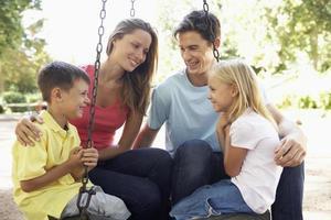 família sentada no balanço no parque infantil