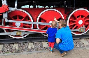 família olhando trem a vapor
