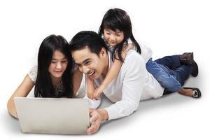 família usando laptop no chão foto