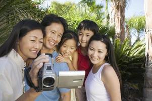 família olhando para a tela da câmera de vídeo foto