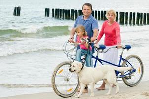 família com cachorro na praia foto