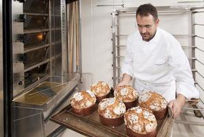 chef de pastelaria colocando alguns bolos no forno foto