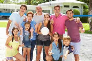 família de várias gerações jogando vôlei no jardim foto