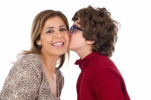 filho beijando a bochecha de sua mãe foto