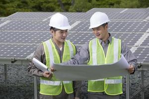 dois engenheiros asiáticos de painéis solares no trabalho. foto