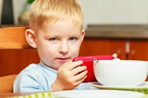 menino criança criança comer flocos de milho café da manhã jogando celular