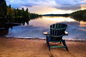 cadeira de madeira ao pôr do sol na praia