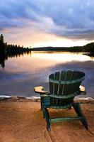 cadeira de madeira ao pôr do sol na praia foto
