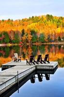 doca de madeira no lago de outono foto