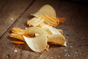 batatas fritas e sal na mesa de madeira velha