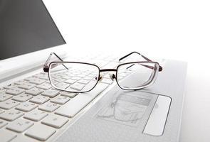 óculos em um teclado de laptop
