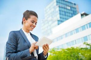 mulher de negócios com o tablet pc no distrito de escritórios foto