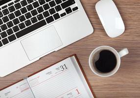 bloco de notas, laptop e xícara de café na mesa de madeira foto