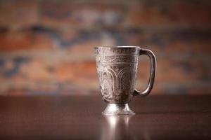 xícara de café de metal com decoração árabe na área de trabalho de madeira