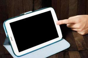 mão segurando um tablet em fundo de madeira foto