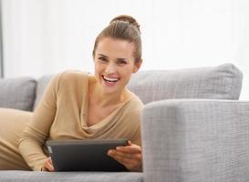 mulher jovem feliz, deitado no sofá com o tablet pc foto