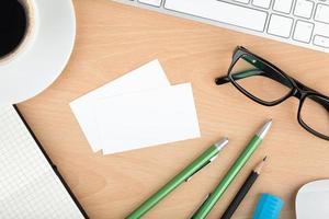 cartões de visita em branco na mesa de escritório de madeira foto