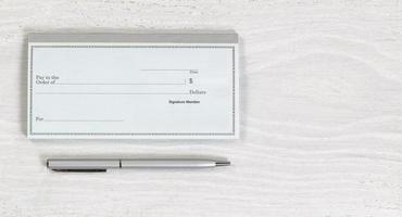 talão de cheques em branco e caneta prata na área de trabalho branca foto
