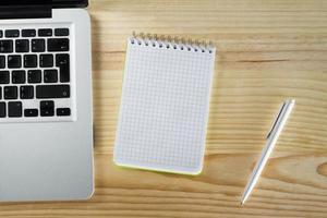 bloco de notas em branco laptop e caneta na área de trabalho de madeira foto