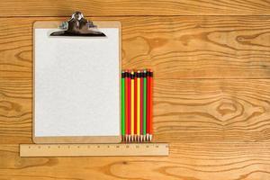 prancheta em branco com papel e lápis coloridos na área de trabalho foto
