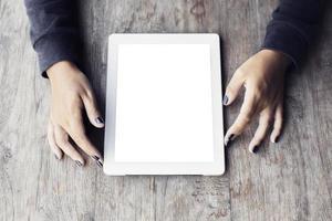 mãos de menina com tablet digital em branco em uma mesa de madeira