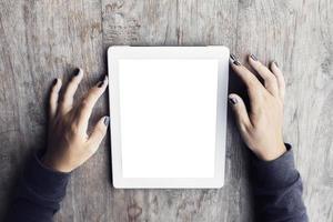 menina com um tablet digital em branco em uma mesa de madeira foto