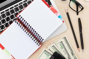 mesa de escritório com pc, suprimentos e dinheiro dinheiro foto