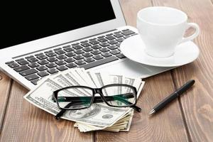 mesa de escritório com pc, xícara de café, copos e dinheiro foto