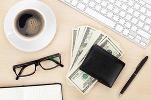 mesa de escritório com pc, suprimentos, xícara de café e dinheiro dinheiro
