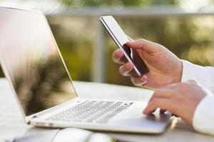 empresário com celular e laptop de manhã foto