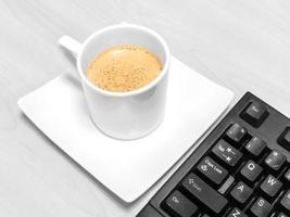 xícara de café e teclado na mesa foto