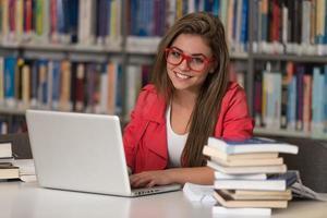 jovem estudante usando seu laptop em uma biblioteca foto
